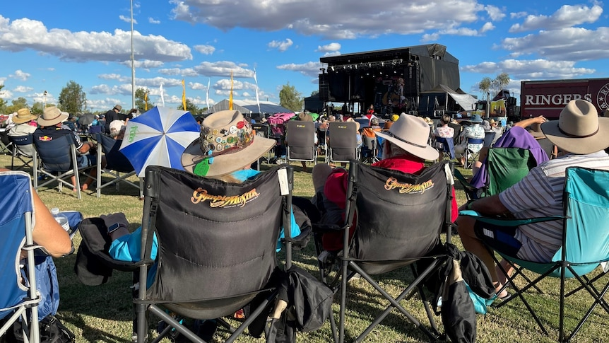 Festival goers sit in camp chairs and watch music acts perform on main stage