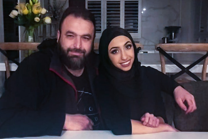 Zain Tiba with his arm around his daughter Ella Tiba at the kitchen table in their home.