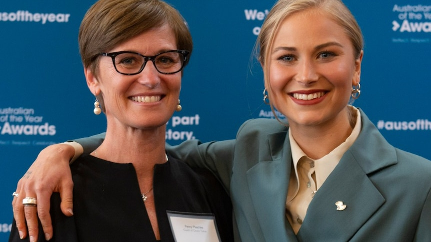 Close up photo of two women smiling at the camera standing in front of the Australian of the Year Awards banner
