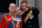 A man appears in a red jacket decorated with medals on the left next to a younger man in a black jacket with some medals too.