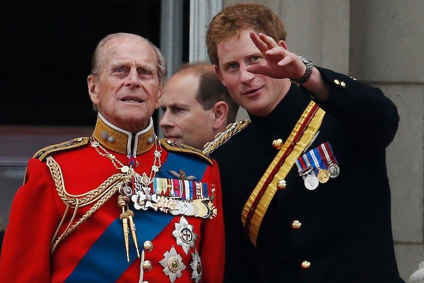 Un bărbat într-o jachetă roșie decorată cu medalii este afișat în stânga lângă un bărbat mai tânăr într-o jachetă neagră, cu câteva medalii, de asemenea.