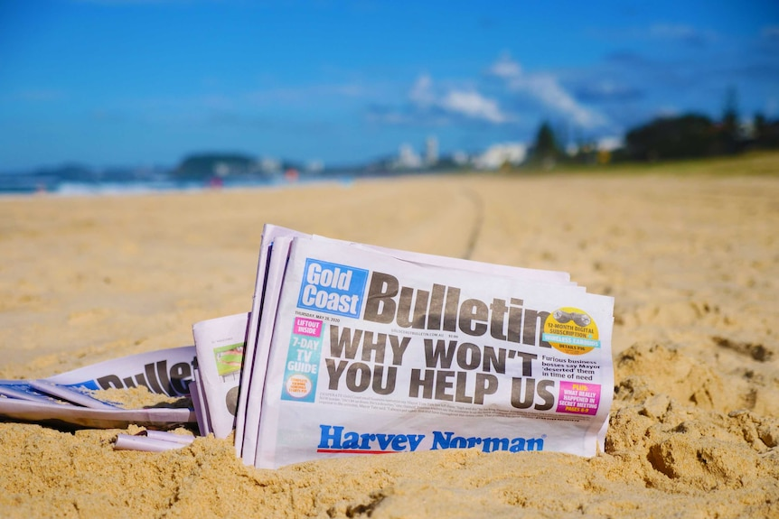 A newspaper – the Gold Coast Bulletin – sits in the golden sand of a sun-drenched beach.