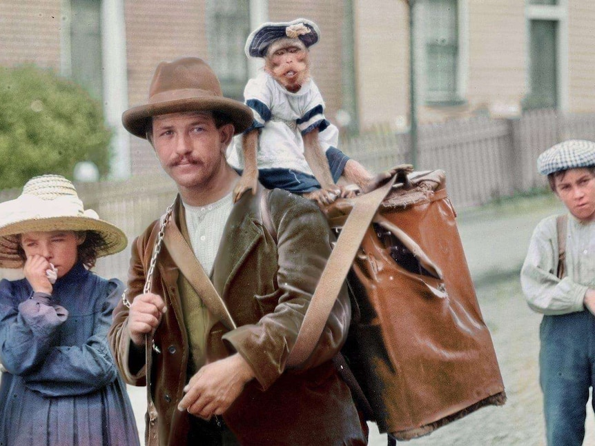 A man surrounded by children has a dressed monkey on his large carry bag.