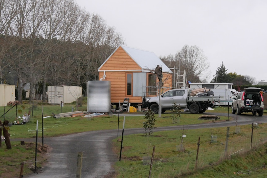 Small home being built at the end of a drive way.