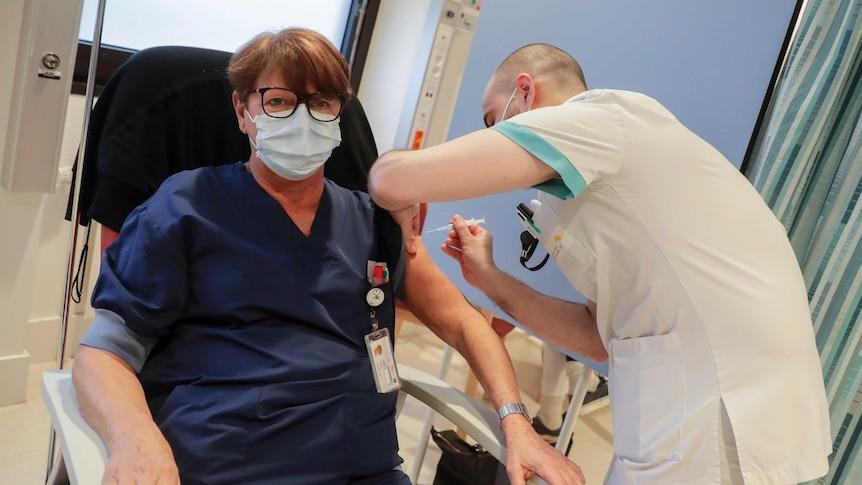 A woman wearing a facemask receives a coronavirus vaccine