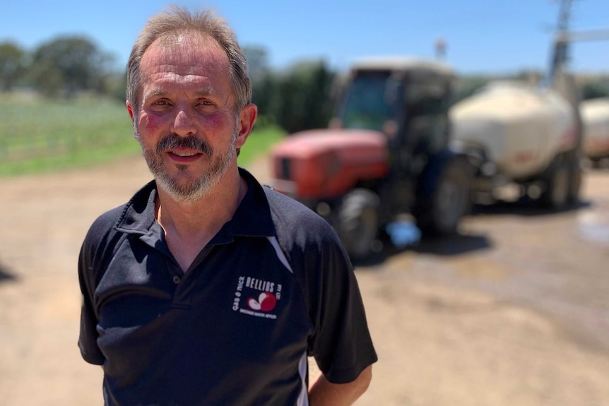 A man with a beard and a tractor behind him.