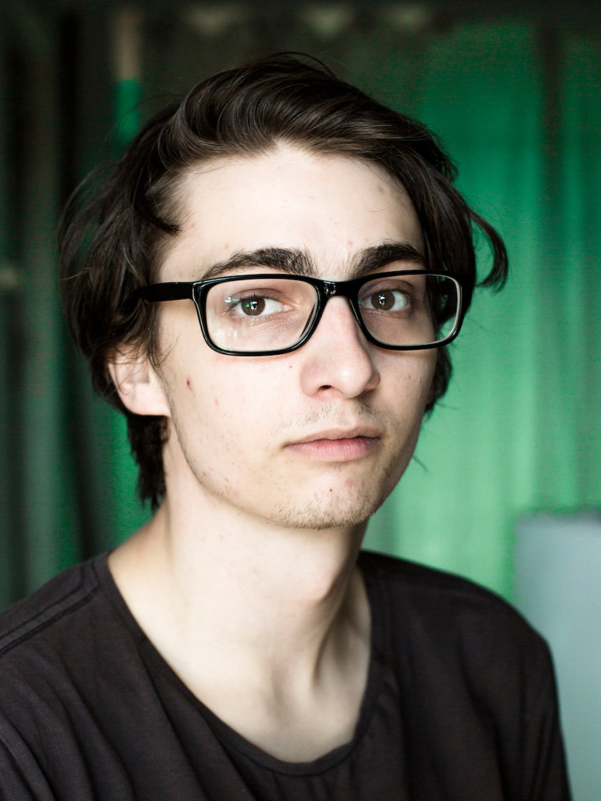 A young man with short dark brown hair and black t-shirt poses in front of out of focus green background, lit by natural light.