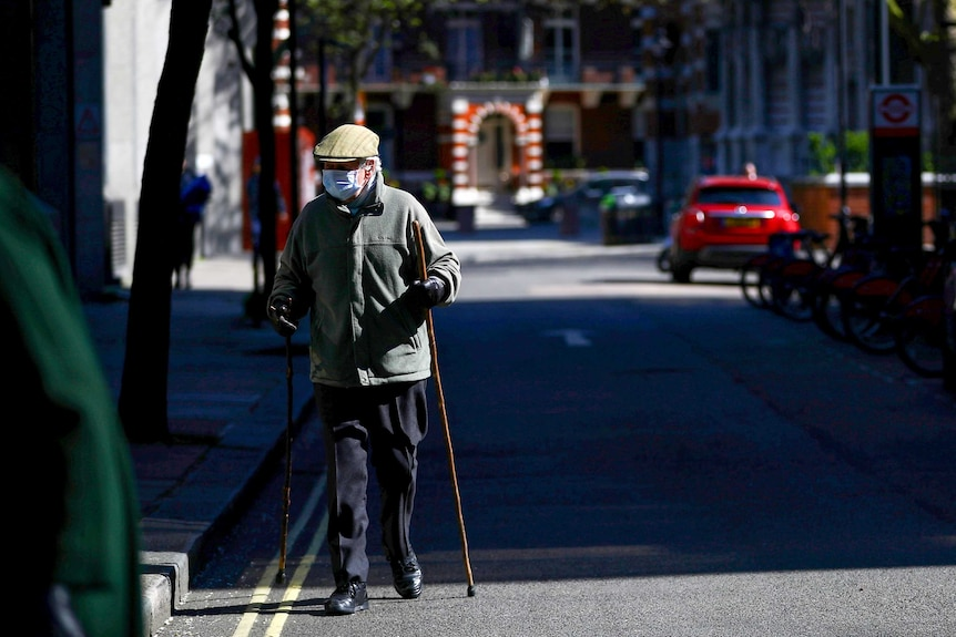 An elderly man with two walking sticks in a face mask