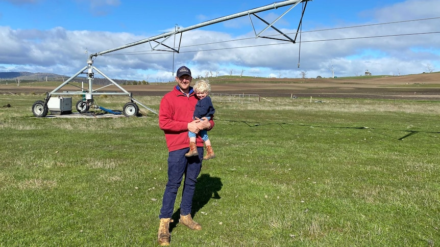 A man holds a child in his arms, and stands in front of an irrigation pivot