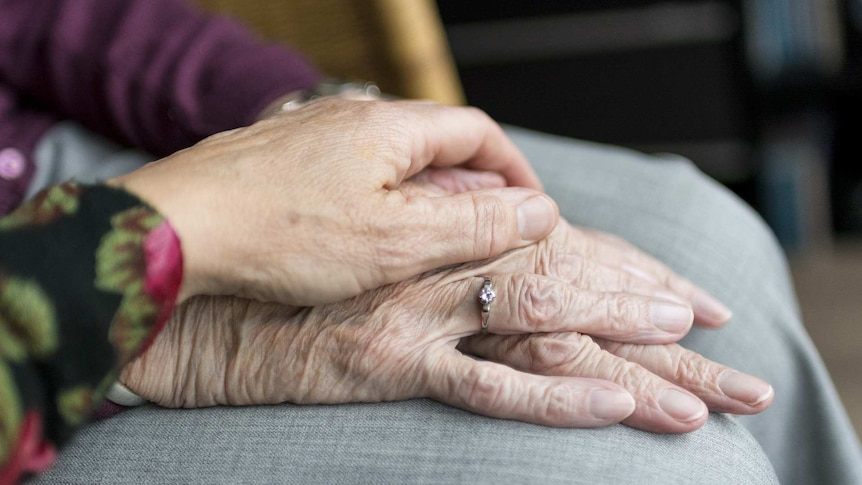 A close-up shot of a hand resting on an elderly woman's hands.