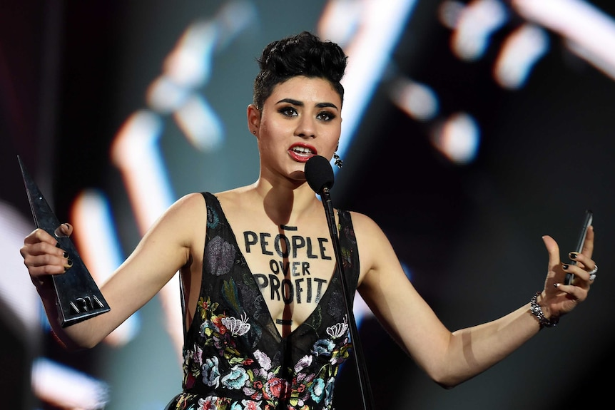 A woman speaks into a microphone while holding an aria award. On her chest is written people over profit.
