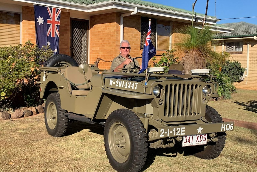 A man sits in an Army jeep parked in the front yard of a house