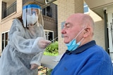 A man getting a COVID-19 test from a nurse wearing a face shield.