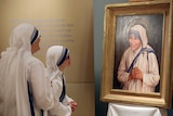 Sisters of the Missionaries of Charity look at the official canonisation portrait of Mother Teresa
