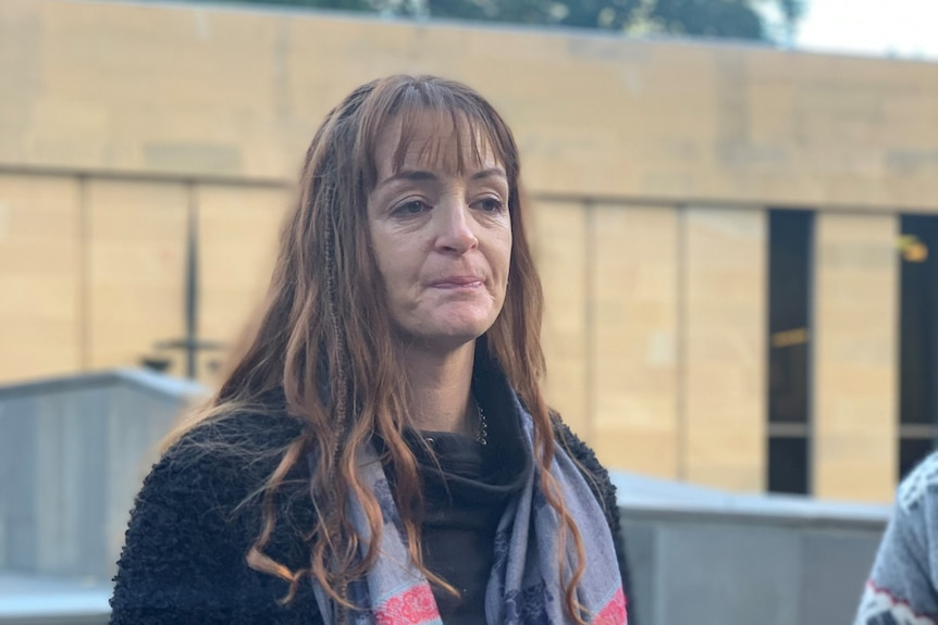 Woman in scarf and woollen coat stands outside Supreme Court
