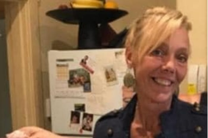 A woman with blonde hair in a kitchen holding up a pizza and smiling.