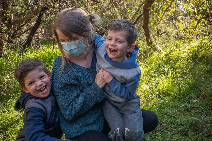 Sarah Robson, wearing a mask, hugs her two sons while standing on green grass surrounded by bush.