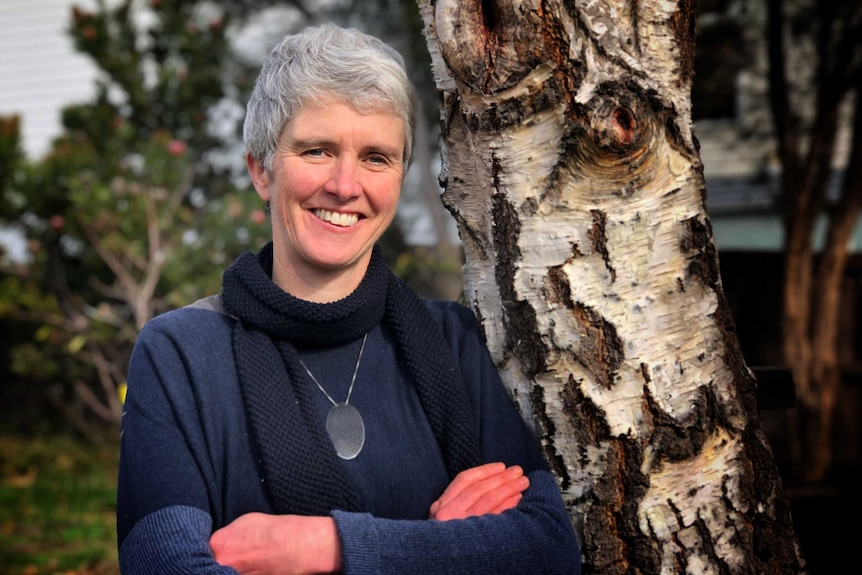 A woman with short grey hair wearing a blue top and scarf stands in front of a birch tree.