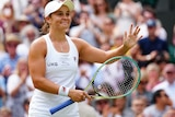 Ash Barty smiles and claps her racquet.
