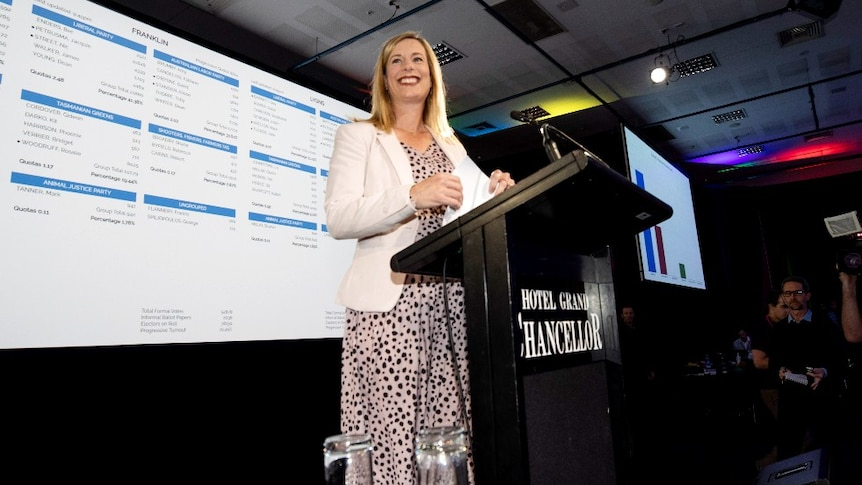 a blonde woman stands on a stage