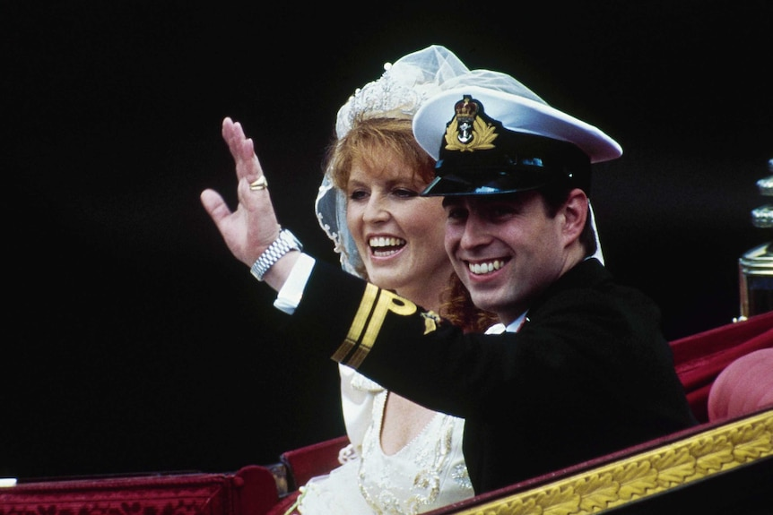 Prince Andrew waves as he sits in a carriage next to Sarah, Duchess of York. He wears black military garb and she wears a gown.