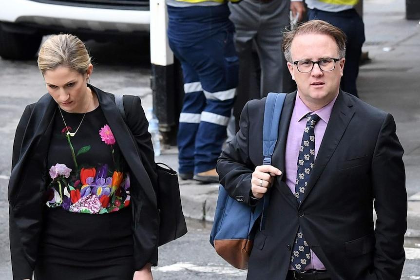 Jonathon Moran and a female arrive at court, walking across a pedestrian crossing