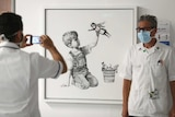 A masked health worker stands next to a painting of a young child playing with a nurse doll wearing a mask and cape