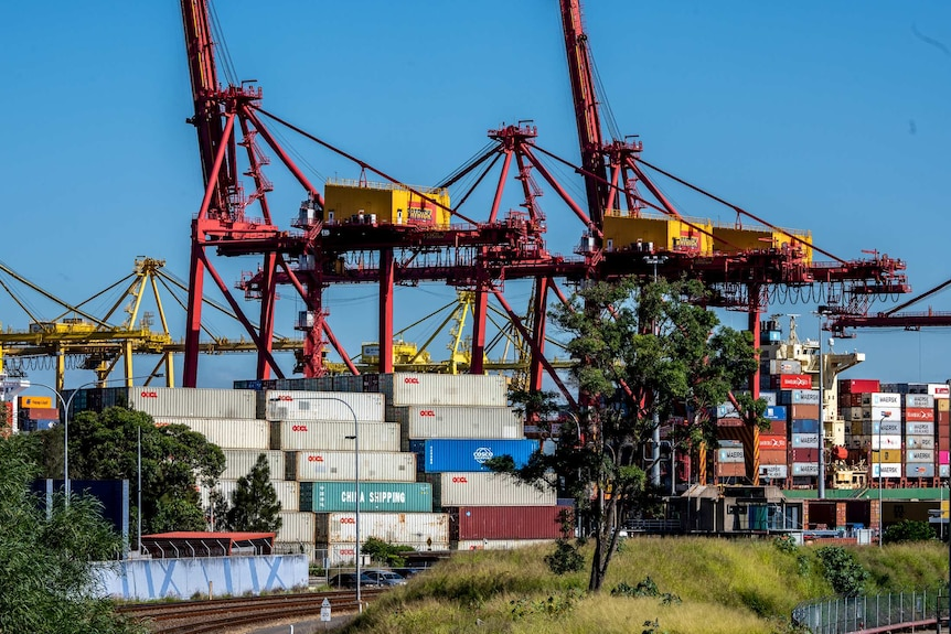 Cranes towering over storage containers at Port Botany.