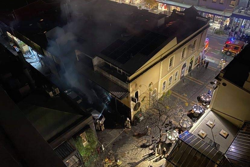 Fire service crews surround a building with smoke rising from its roof
