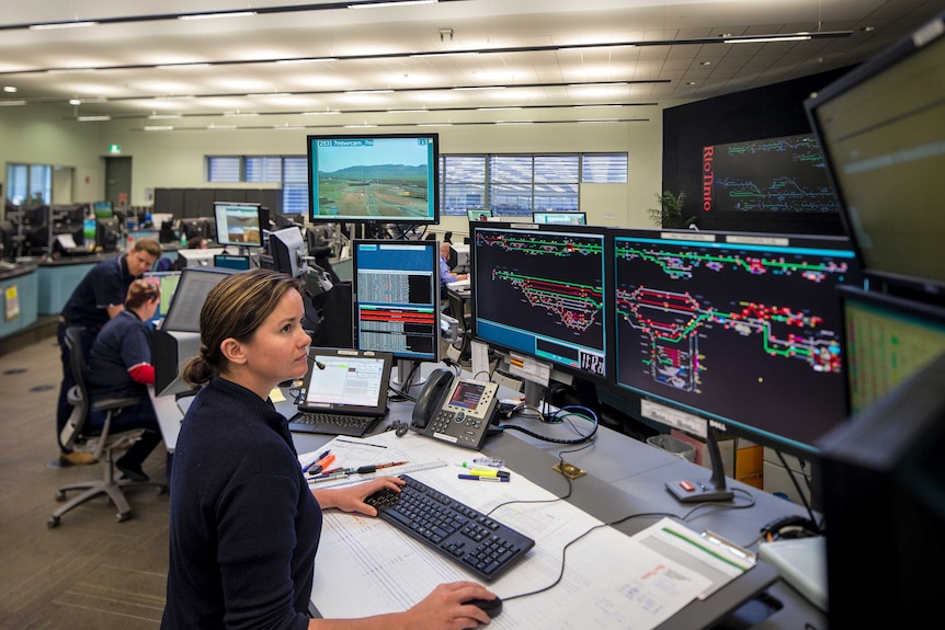 Workers in front of banks of computers and monitors remotely running operations at  Rio Tinto iron ore mines in WA