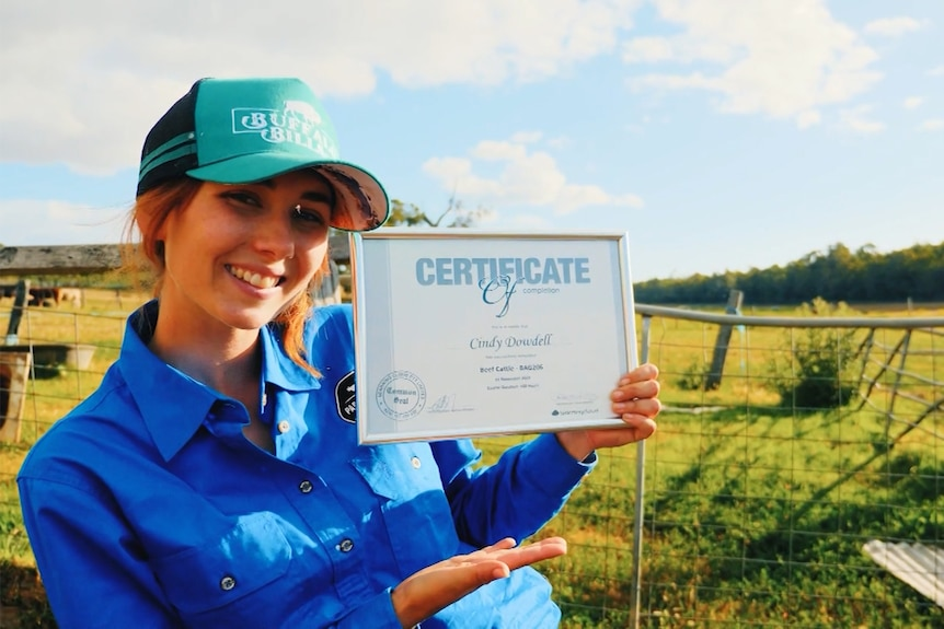 A woman stands in a field with a farm gate behind her, while wearing a blue hat and shirt and smiles as she holds a certificate