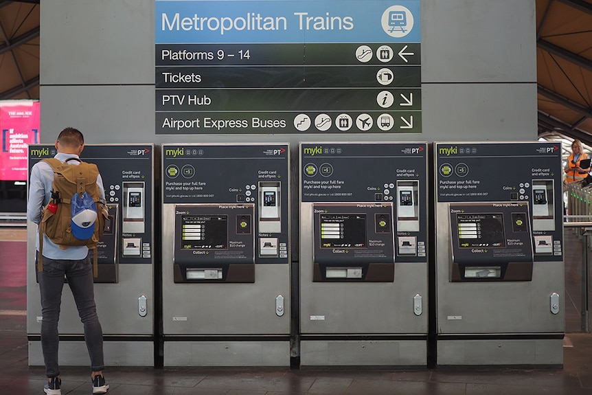 A man with his back to the camera uses one of four myki machines below a sign directing people to regional and metro trains.