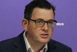Victorian Premier Daniel Andrews standing at a lectern in front of microphones with a purple backdrop.