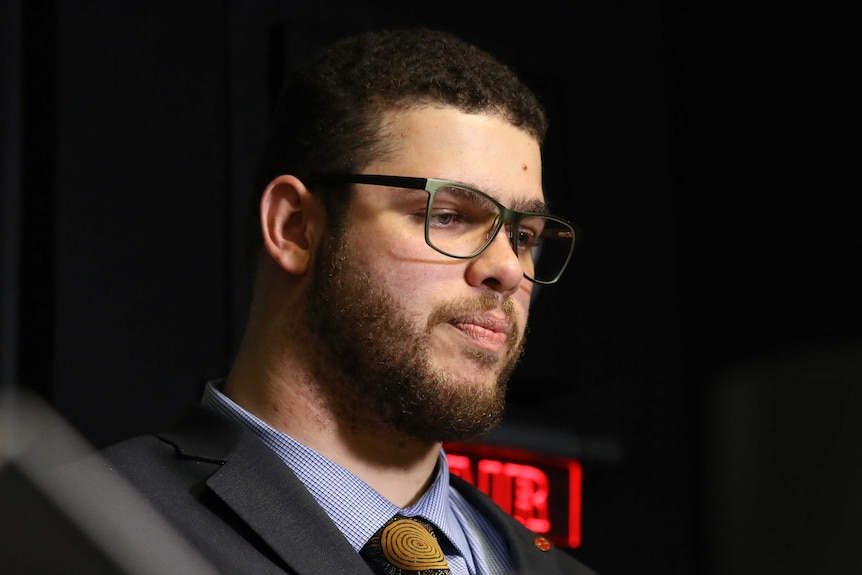 A close-up shows Jordon Steele-John's face as he purses his lips and looks down. There is a red 'on air' light behind him.