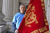 A man with greying hair smiles as he holds a large red flag with a golden dragon embroidered on it.
