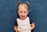 A young girl smiles while standing against a blue wall indoors looking at the camera, wearing a cream jumpsuit and dark shirt.