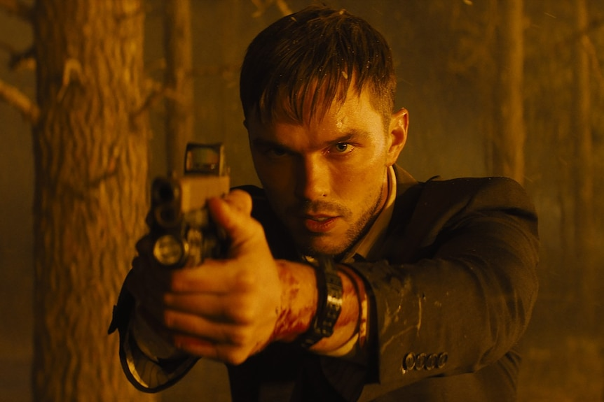 Film still of Nicholas Hoult as Patrick holding a gun in front of a forest fire in Those Who Wish Me Dead
