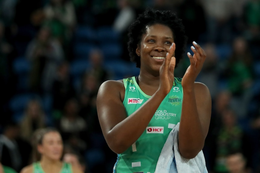 Jamaican player claps hands together after game with smile on face to thank fans
