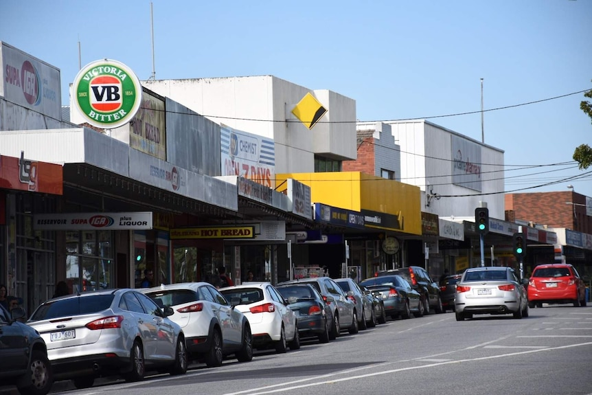 Cars are parked on the street outside the Reservoir SUPA IGA. There is a Commonwealth Bank, chemist and bakery.