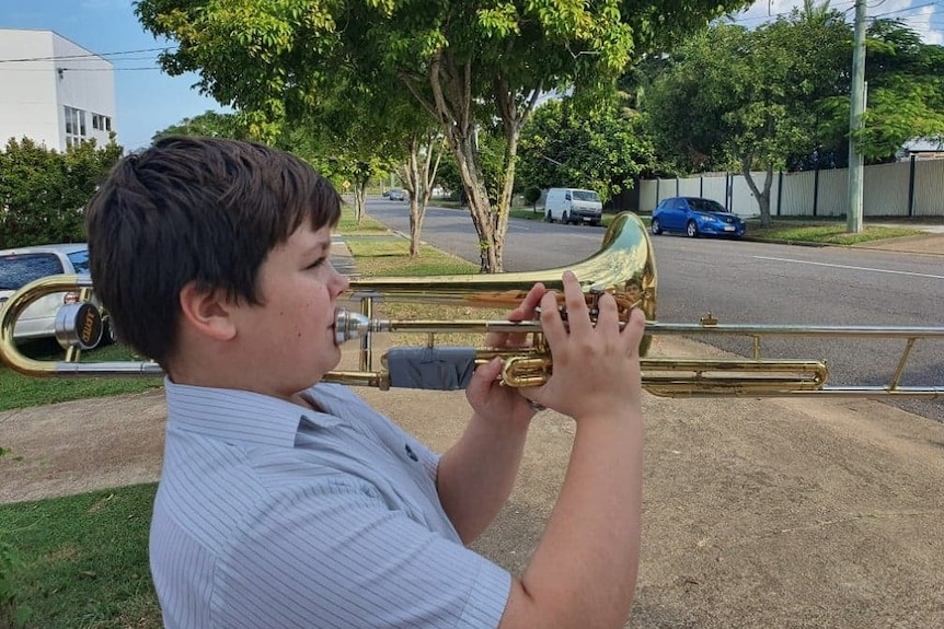 A boy playing a trombone at the end of a suburban driveway
