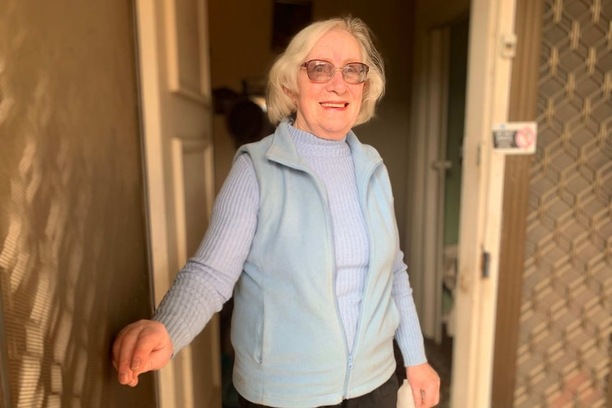 A light-haired woman wearing glasses stands on her doorstep and looks into the camera.