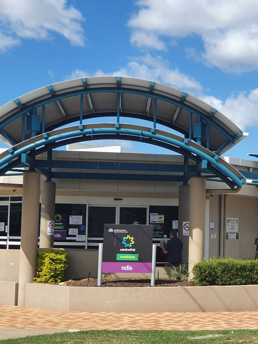 A Centrelink building with a line of about a dozen people outside.