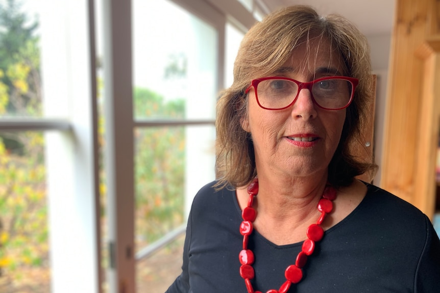 Sarah Russell wearing red glasses and a necklace, looking at the camera in a portrait taken indoors.
