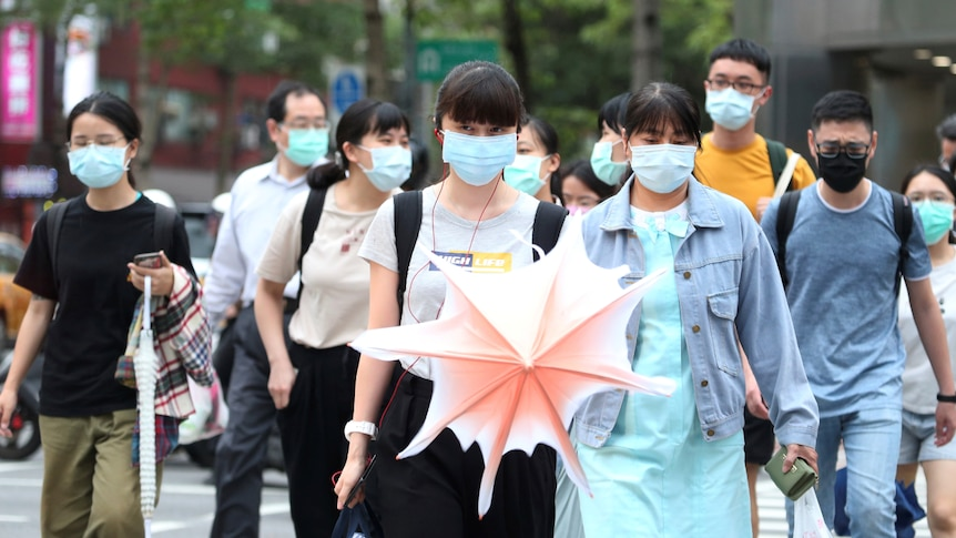 A group of people wearing face masks walks down the street.