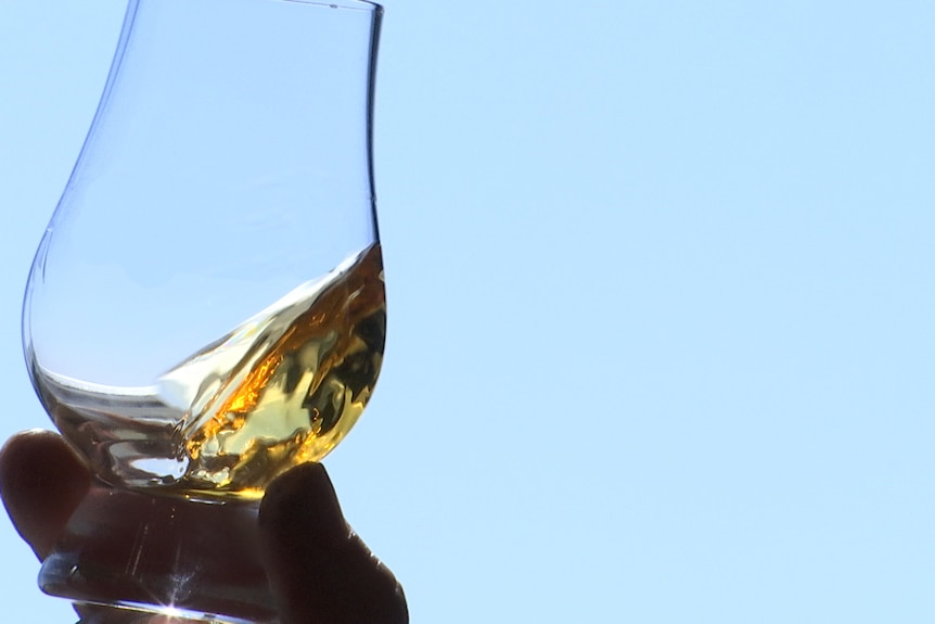 A hand holds a glass of whisky up to the light.