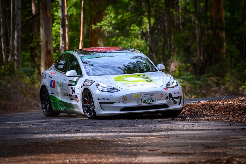 A white car decorated with advertising stickers, driving in a forest