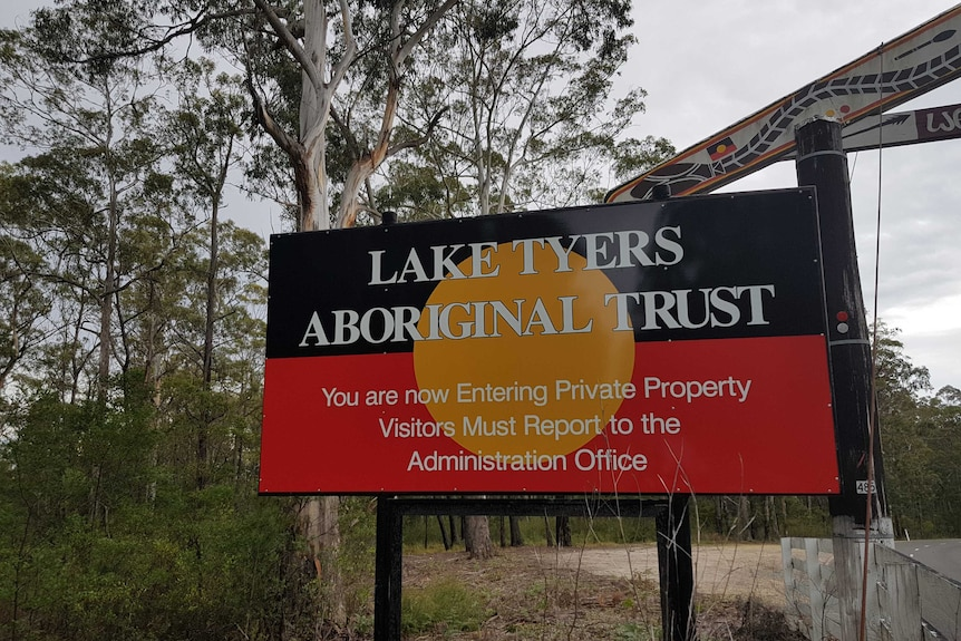 """A sign with """"Lake Tyers Aboriginal Trust"""" written on an Aboriginal flag background."""