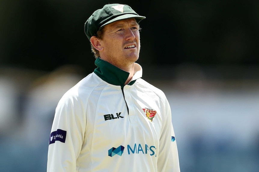 A Tasmanian Sheffield Shield player stands in the field as he looks towards the sky against Western Australia at the WACA.