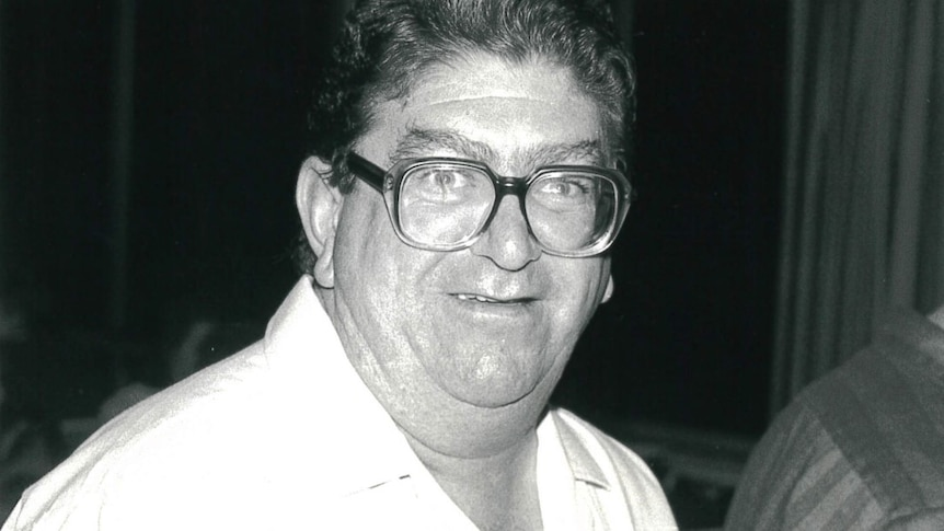 A portly man with thick, squarish glasses smiles.