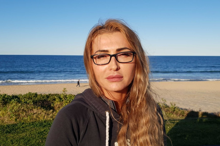 Aneta Duncan, wearing a dark hoodie top and black-rimmed glasses, sitting with a beach and ocean in the background.